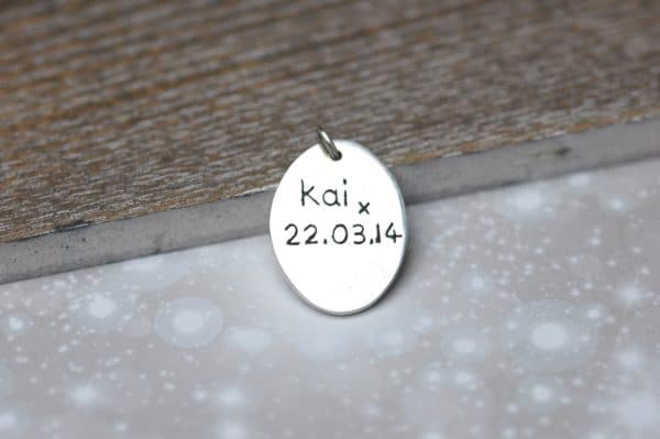 Inscription on the back of a silver oval paw print charm