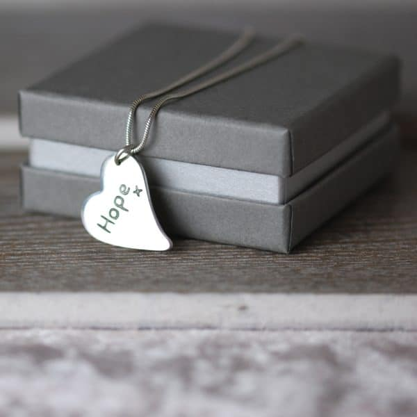 Inscription on the back of a silver curved heart paw print charm