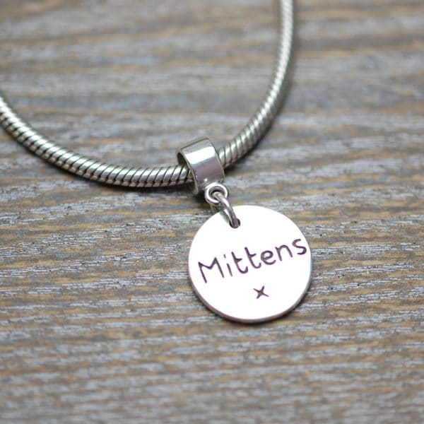 Inscription on the back of silver paw print charm