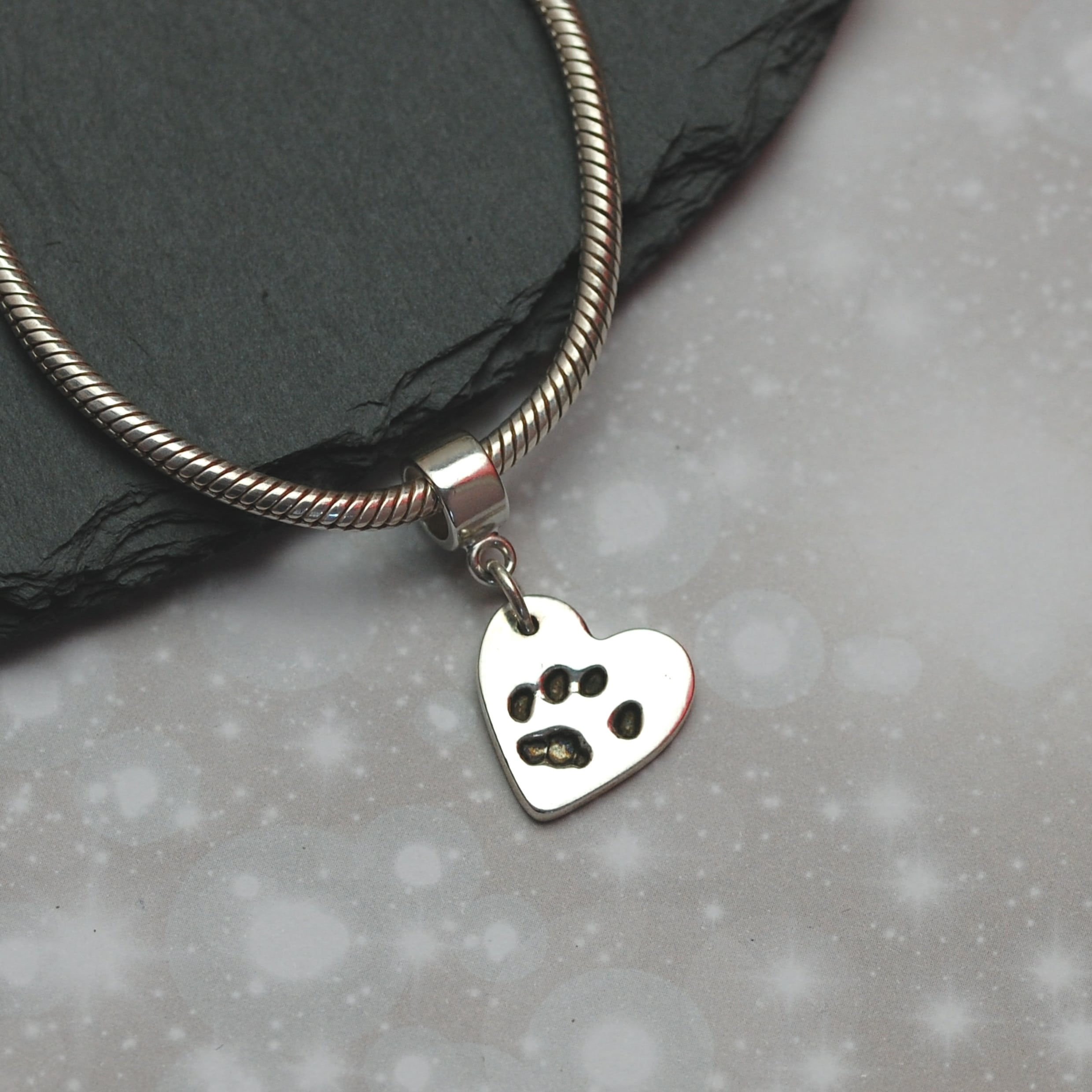 Small silver paw print charm with charm carrier
