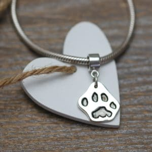 Small silver cut out paw print charm with charm carrier