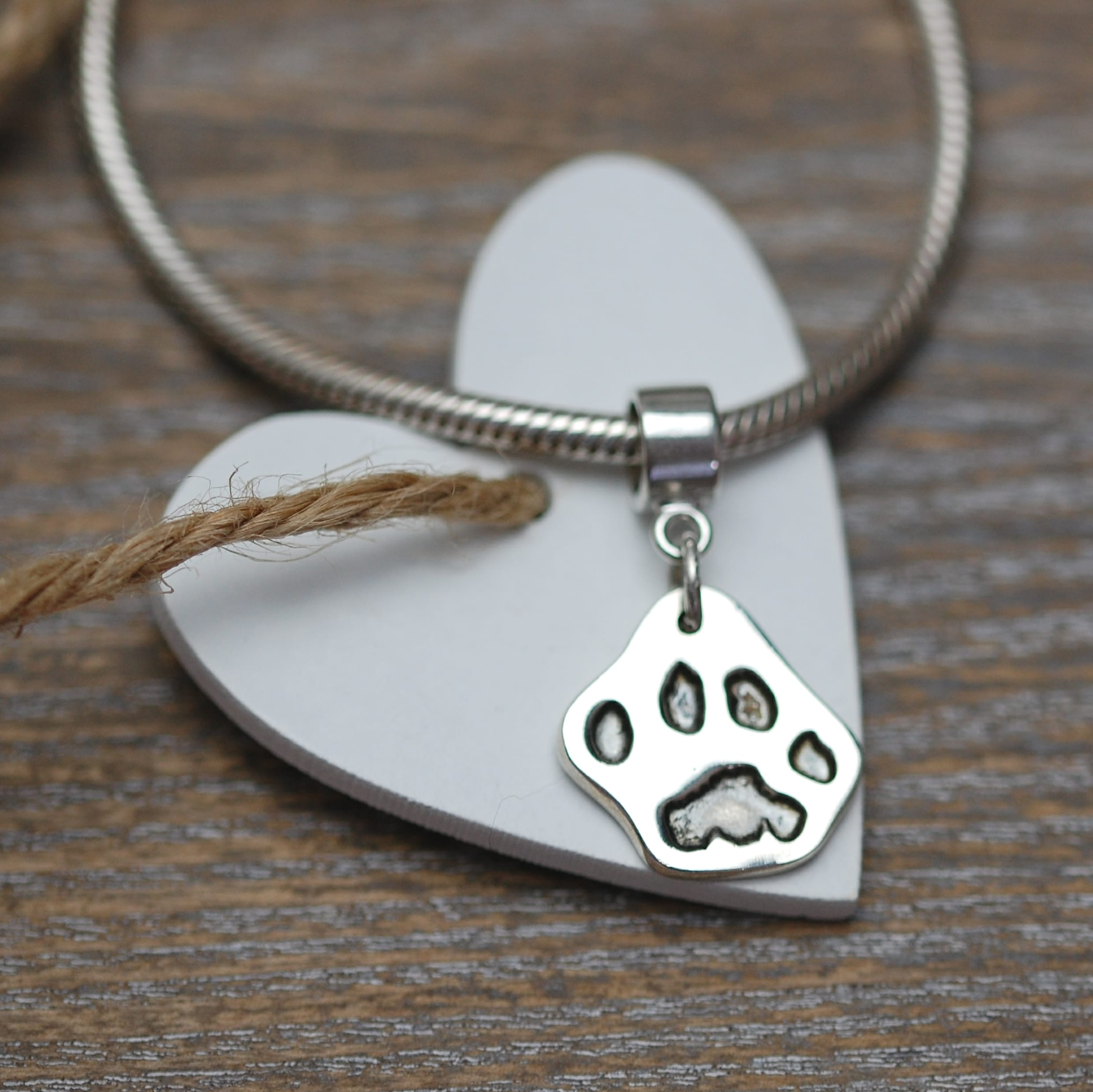 Small silver cut out paw print jewellery charm with charm carrier