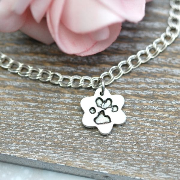 Silver flower paw print charm on a bracelet