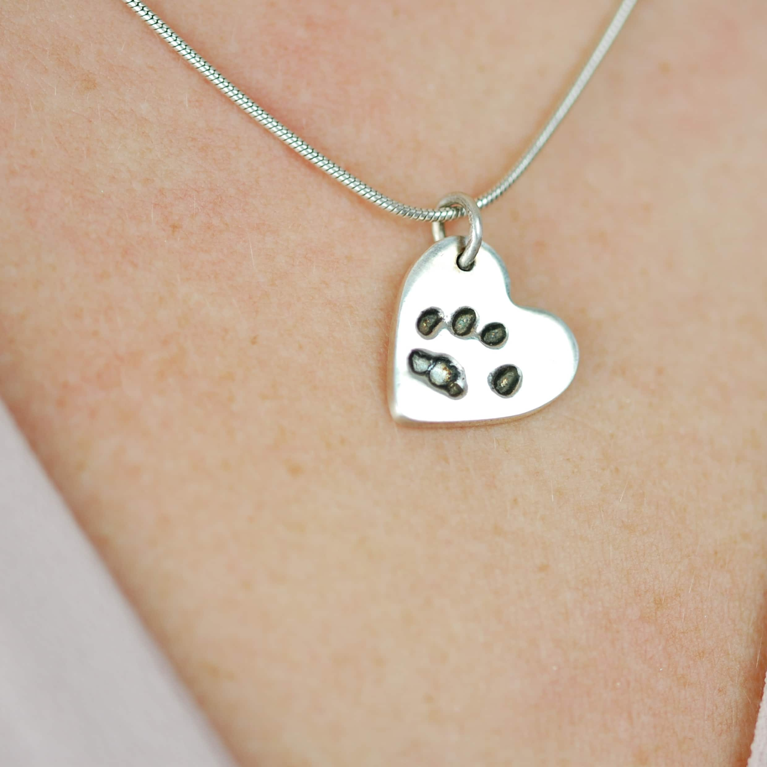 Small silver heart paw print charm on a snake chain