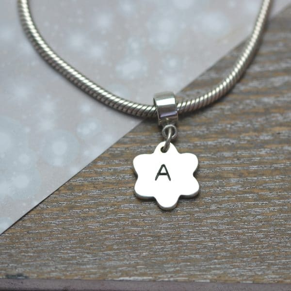 Small silver charm with initial hand inscribed