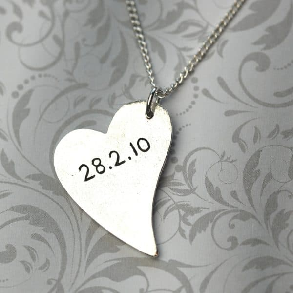 Inscription on the back of a silver raised paw print charm
