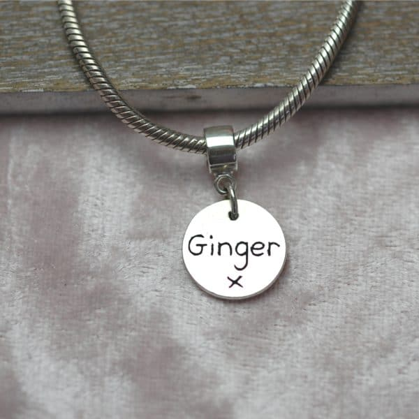 Inscription on the back of raised paw print charm with charm carrier