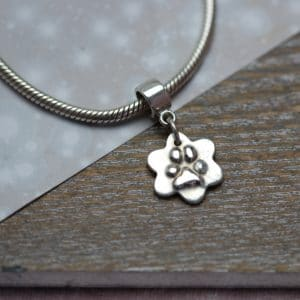 Small silver flower with raised paw print and charm carrier