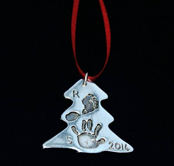Silver Christmas tree charm with hand & footprint, initial and the year on the front. Presented on red ribbon ready to hang.