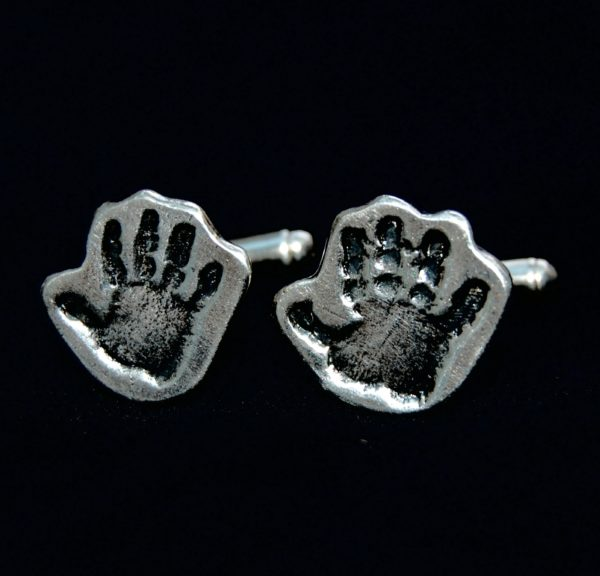 Silver cufflinks cut by hand in the shape of the handprints. Initials hand inscribed on the back.