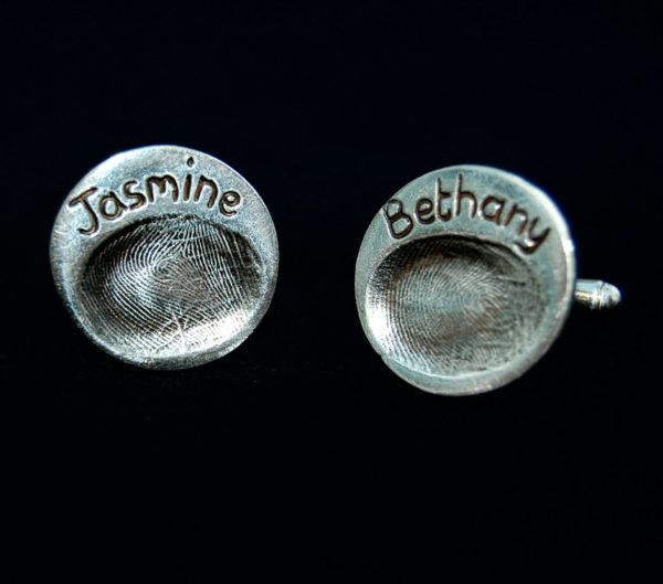 Circle shaped silver fingerprint cufflinks with names hand inscribed above the fingerprints.