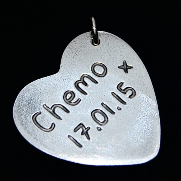 Name and special date inscribed on the back of a large heart charm.