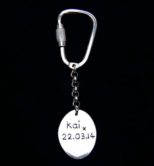 An inscription on the back of an oval 'say it in silver' keyring.