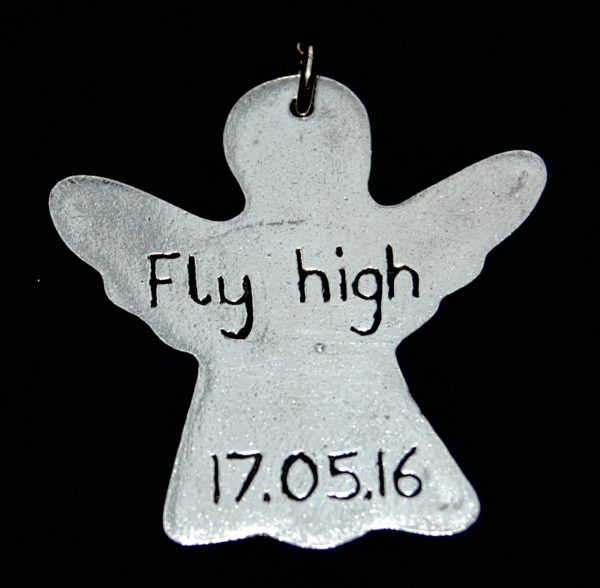 Inscription on the back of a silver angel footprint charm.