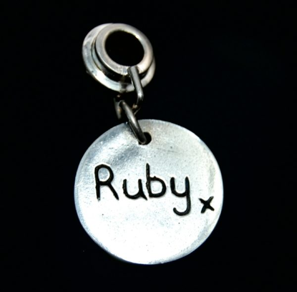 Small silver circle 'say it in silver' charm with name hand inscribed.