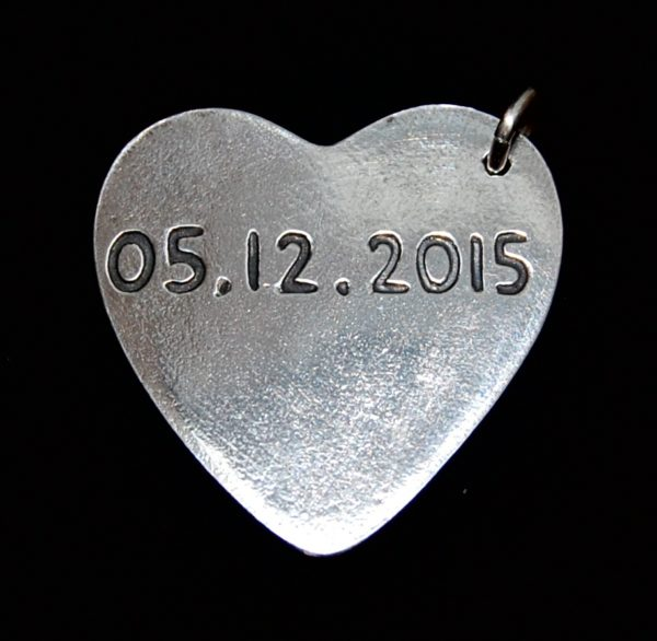Special date hand inscribed on the back of a charm.