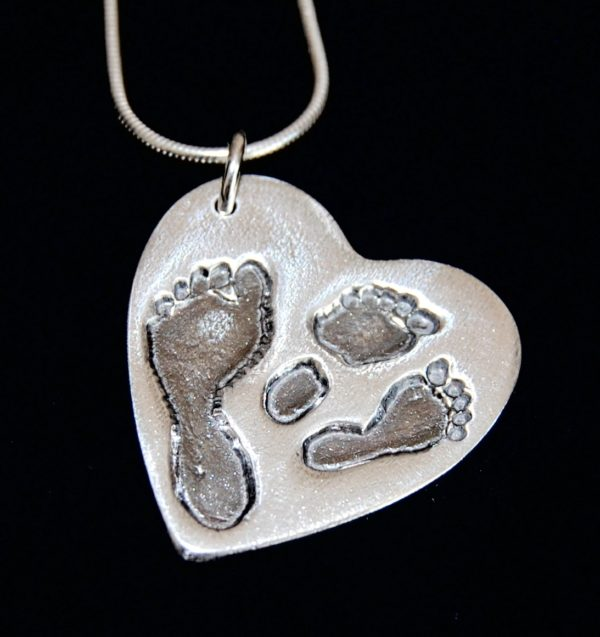 Large silver heart charm with footprints from a set of twins and their older sibling. Names are hand inscribed on the back.
