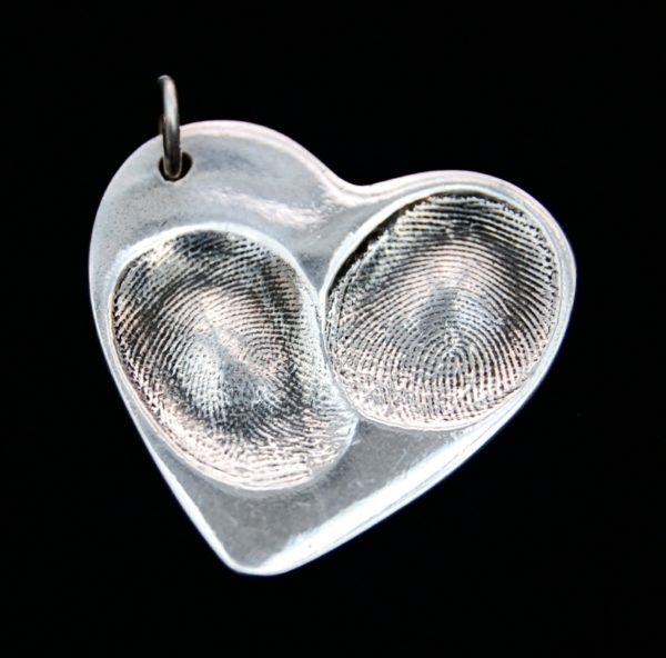 Large heart shaped fingerprint charm showcasing prints on the front and names hand inscribed on the back.