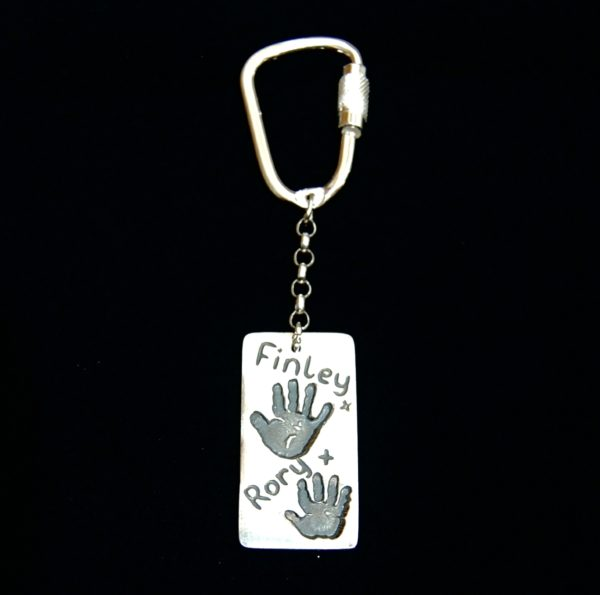 Large silver rectangle handprint keyring. Handprints and names hand inscribed on the front.