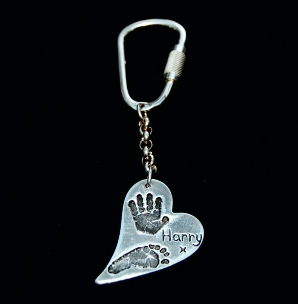 Large silver curved heart hand and footprint kering. Name hand inscribed alongside the prints.