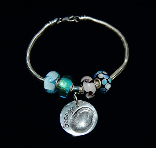 Regular circle shaped silver fingerprint charm presented on a charm carrier. Bracelet can be purchased separately from the Accessories section.