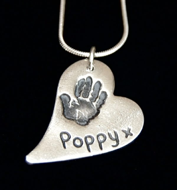 Regular silver curved heart handprint charm with name hand inscribed alongside the print.