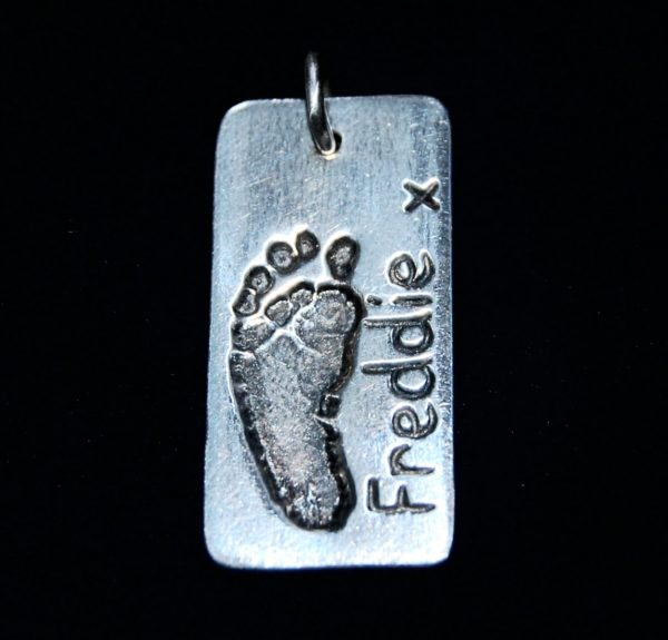 Regular silver rectangle footprint charm with name hand inscribed alongside.