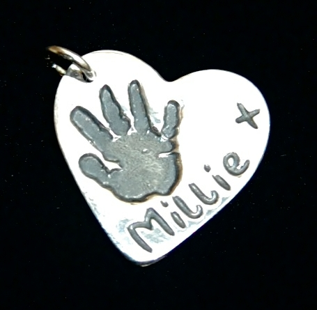 Regular silver heart handprint charm with name hand inscribed on the back.