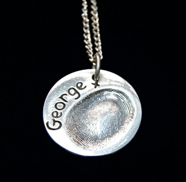 Regular circle shaped silver fingerprint charm with name hand inscribed on the front.