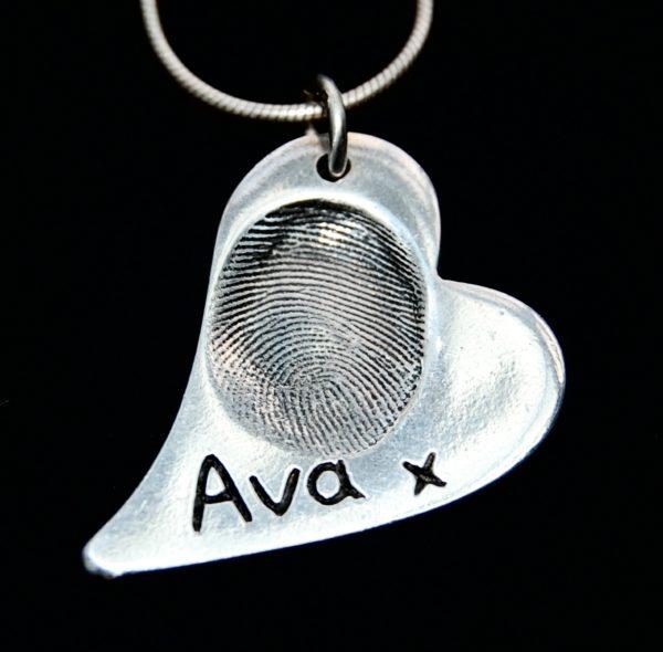 Regular curved heart shaped silver fingerprint charm with name inscribed alongside the fingerprint.