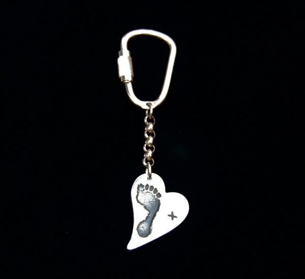 Regular silver curved heart footprint keyring inscribed with a simple but effective kiss on the front and name on the back.