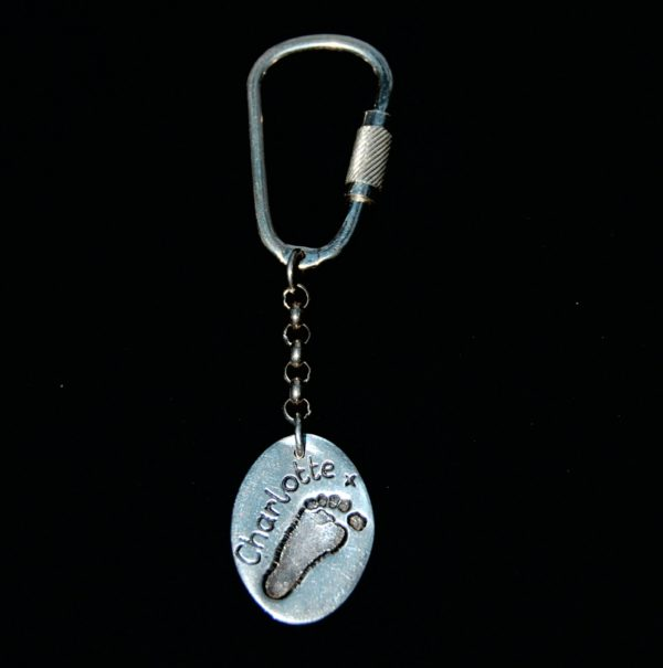 Regular silver oval footprint keyring personalised with name on the front.