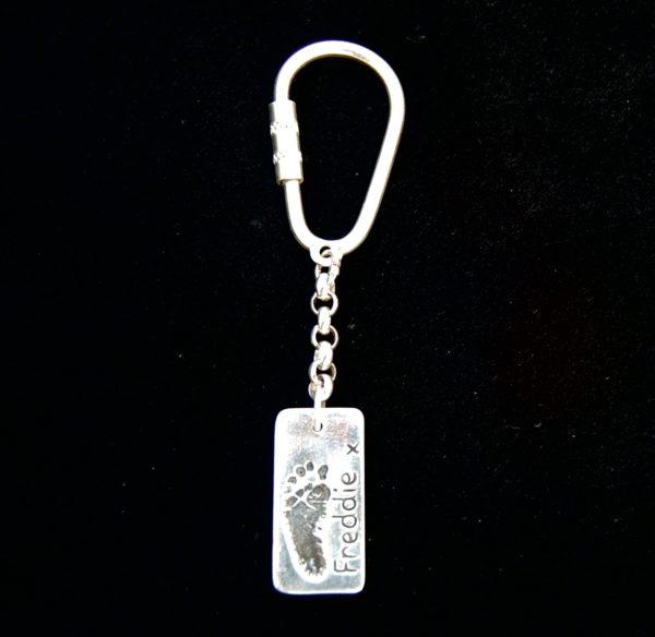 Regular silver rectangle footprint keyring. Name hand inscribed alongside footprint.