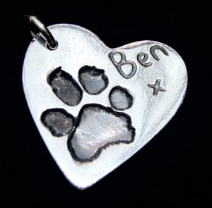 Regular silver heart paw print charm with name hand inscribed on the front.