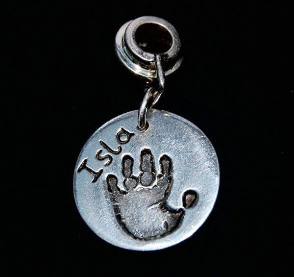Regular silver circle handprint charm presented on a charm carrier.