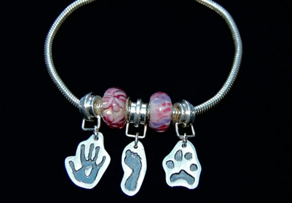 Pandora style bracelet with cut out hand, foot and paw print charms. Names hand inscribed on the backs of the charms.
