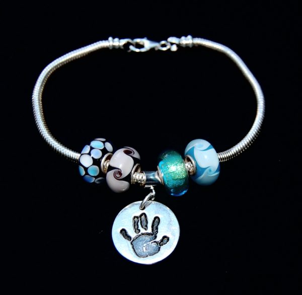 Small silver circle handprint charm with Pandora style charm carrier. Pandora style bracelet can be purchased separately.