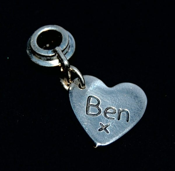 Small silver heart charm with name hand inscribed. Presented on a charm carrier ready to add to a bracelet or necklace.