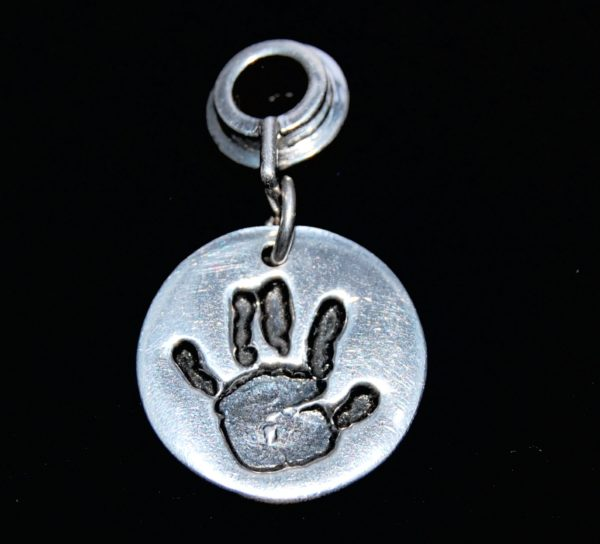 Small silver circle handprint charm presented on a charm carrier. Name is hand inscribed on the back.