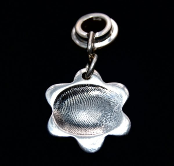 Small flower shaped silver fingerprint charm with name hand inscribed on the reverse. Charm secured attached to a charm carrier. Bracelets can be purchased separately.