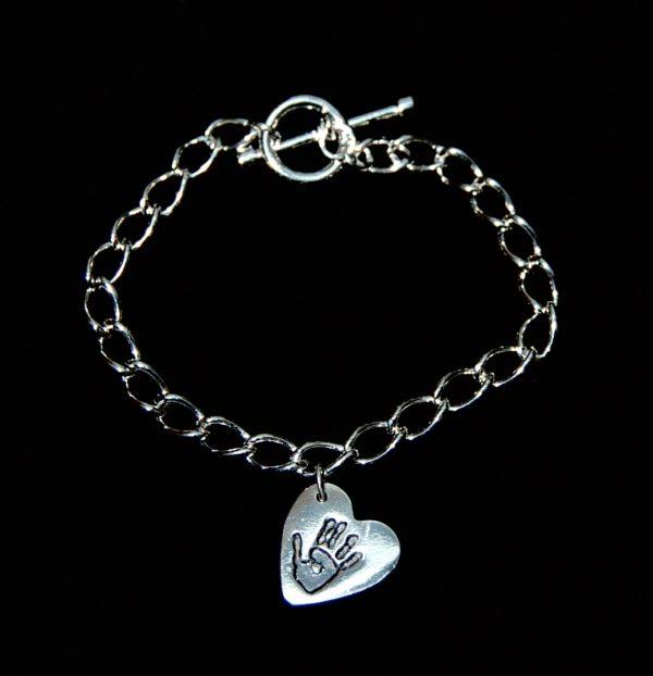 Small silver heart handprint charm on a T-bar curb chain bracelet.