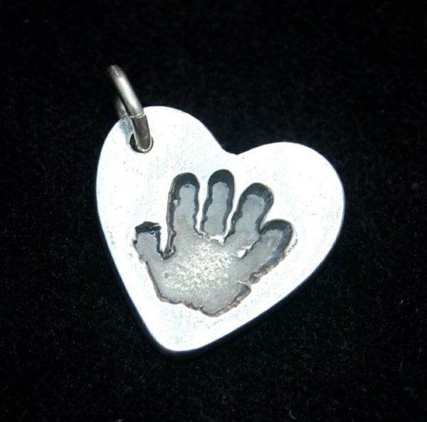 Small heart shaped silver handprint charm with name hand inscribed on the back.