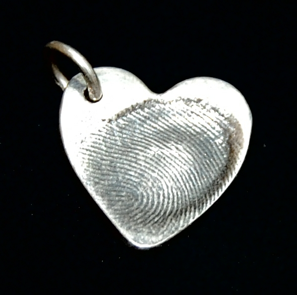 Small heart shaped silver fingerprint charm with name hand inscribed on the reverse.