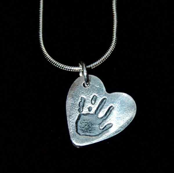 Small silver heart handprint charm on a sterling silver snake chain. Name hand inscribed on the back.
