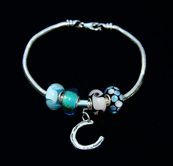 Small silver horse shoe cut out charm with charm carrier. Bracelet can be purchased separately.