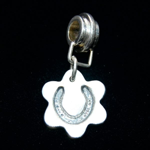 Small silver flower charm with your horse's shoe imprint. Securely attached to a charm carrier ready to add to your bracelet.