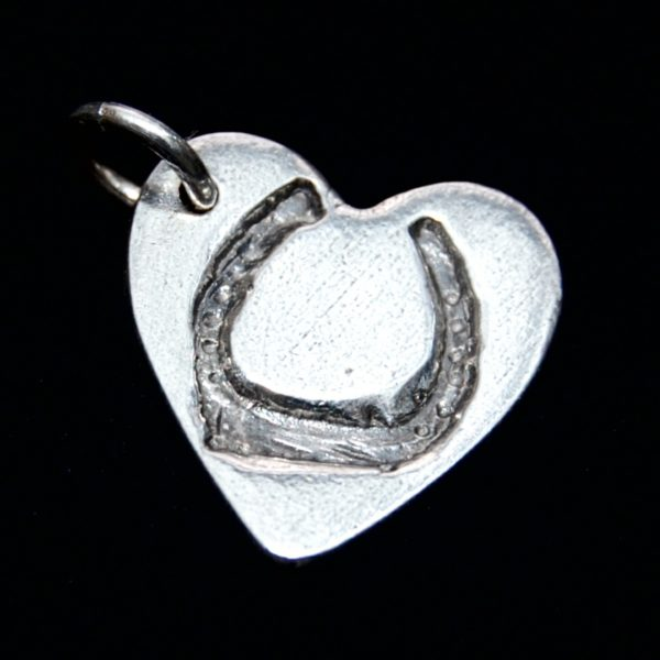 Small silver heart charm with horse shoe imprint on the front and name hand inscribed on the back.