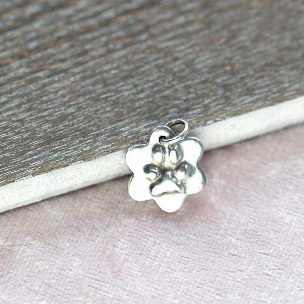 Smal silver flower charm with raised paw print
