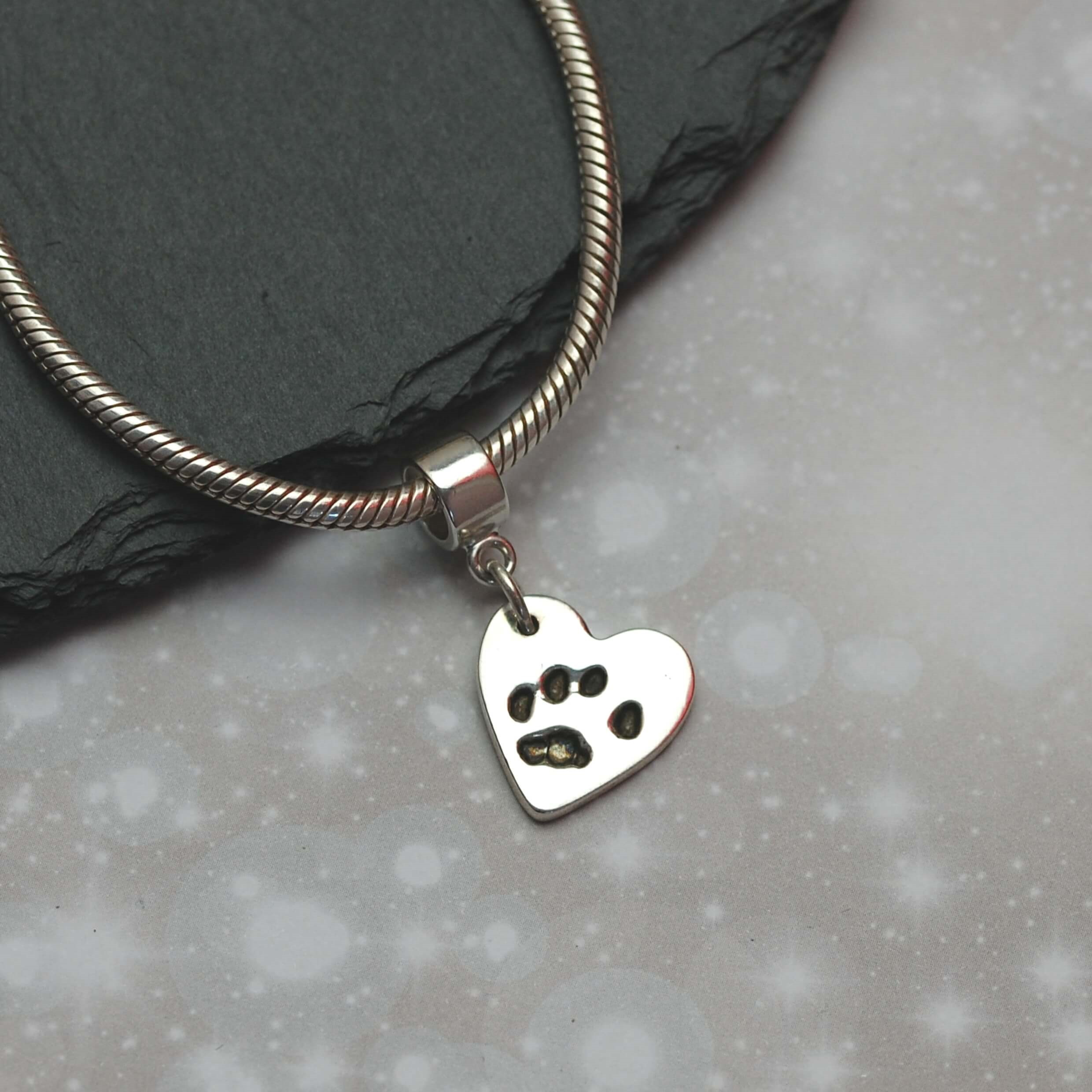 Small silver paw print charm created from silver clay