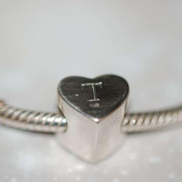 Initial engraved on the back of silver heart charm bead with pet fur or cremation ashes